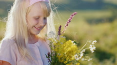 Funny girl 5 years old with a bouquet of flowers. She smiles looking at the Stock Footage