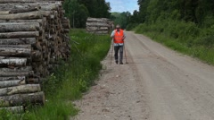 Hiker walking with walking sticks on the forest road Stock Footage