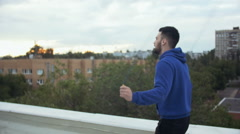 Young Male Athlete Jumping By The Skipping Rope On The Roof. Cinematic - stock footage