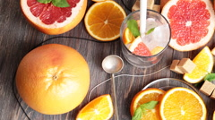 Cold citrus drink surrounded by grapefruit halves and segments, orange slices Stock Footage