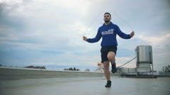 Young Male Athlete Jumping By The Skipping Rope On The Roof. Slow-Mo. Cinematic - stock footage