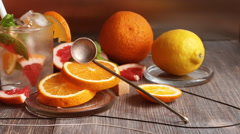 Cold citrus drink surrounded by various citrus fruits Stock Footage