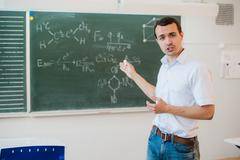 Young teacher near chalkboard in school classroom talking to class Kuvituskuvat