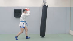 Young Fighter Trains With Punching Bag In The Gym. Slow-Mo Stock Footage