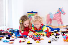 Little kids playing with toy cars - stock photo