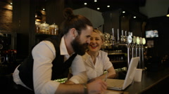 4K Bar owner working on laptop & discussing business plan with female colleague - stock footage