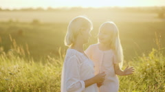 A blonde girl playing with her mother - combing her hair. In the meadow at Stock Footage