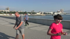 Two Men and Women Are Walking on Different Side in Sunny Embankment Stock Footage