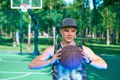 Man with basketball ball standing on playground Stock Photos