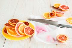 Citrus fruits and knife on wooden table. Recipe concept Stock Photos