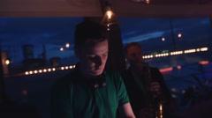 Dj dance at turntable on party in nightclub. Headphones. Man play saxophone Stock Footage