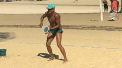 A player practices for a beach tennis game on copacabana beach in rio Stock Footage