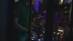 Dj spinning at turntable on party in nightclub. Equipment. Saxophonist. Lights - stock footage