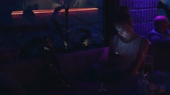 Girl sitting at table with phone on party in nightclub. Dance. Cheer. Lights - stock footage