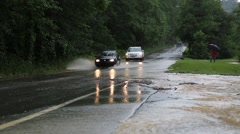 Cars Approaching on Street with Flooded Ditch Line Stock Footage