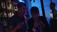 Men drink cocktail, speak using phone on party in nightclub. Spotlight. Cheering - stock footage