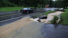 Flooded ditch with cars passing on road - stock footage