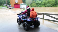 Three People on Four Wheeler Passing through Flood Waters Stock Footage