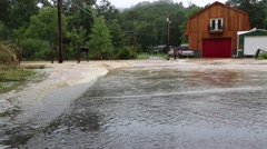 Low Angle of Flood Waters Passing Over Road Stock Footage