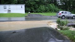 Car Passing as Flood Water Flow over Driveway Stock Footage