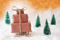 Christmas Sleigh With Orange Background On Snow Stock Photos