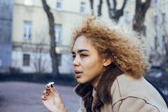 young pretty girl teenage outside smoking cigarette, looking like real junky - stock photo
