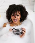 young afro-american teen girl laying in bath with foam, wearing swag jewelry - stock photo