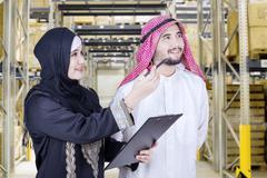 Arabian businesspeople look at warehouse - stock photo