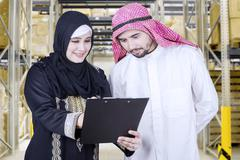 Arabian woman shows document at her partner Stock Photos
