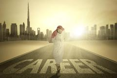 Arabian worker runs with Career word Stock Photos
