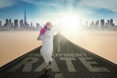 Arabic man and Employment Rate text at road - stock photo