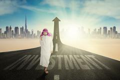 Cheerful Arabian worker with Investment word - stock photo