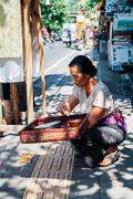 Balinese woman making offerings to the Gods - stock photo