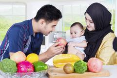 Family and baby cooking healthy food - stock photo