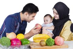 Father giving an apple to baby - stock photo