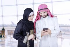 Two Arab workers use cellphone in airport Stock Photos