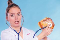 Dietitian examine sweet roll bun with stethoscope. Stock Photos