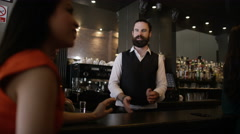 4K Friendly barman serving drinks & group of friends chatting in city bar Stock Footage