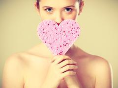 Naked woman holding heart shaped sponge - stock photo
