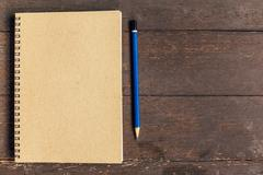 Brown book and pencil on wood table background with space Stock Photos