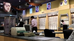 Customer asking some questions to optician at Image Optometry store Stock Footage