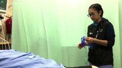 Nurse wearing gloves before drawing blood sample at ER ward - stock footage