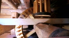 Closeup on moving wooden mechanism and gear wheels on restored flour mill. - stock footage