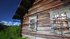 Old wooden house with closed windows and far off meadow. - stock footage