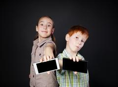 Happy girl and unhappy boy, children show mobile phone screen - stock photo