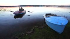 Two fishermen moore on sunset after fishing on the lake. Stock Footage