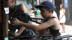 Girl is Helping Boy to Shoot in Shooting Range in Attraction Park Stock Footage
