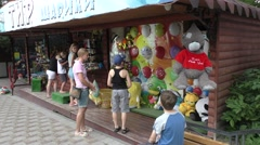 Woman and Two Boys Are Standing Near Attraction With Multi Colored Air Balloons - stock footage