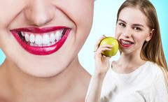 Young woman with brackets on teeth eating apple - stock photo