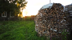 Beautiful firewood footage in the yard. Green meadow on the sunset. Stock Footage